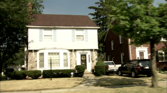 a suburban neighborhood features streets lined with large, two story houses. available in hd. - zweistöckiges wohnhaus stock-videos und b-roll-filmmaterial
