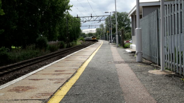 suburban train goes through a deserted station in essex england - station stock videos & royalty-free footage