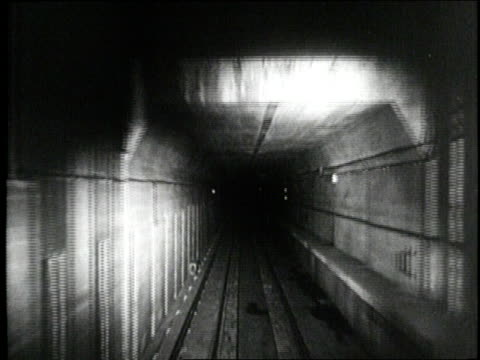 A subway approaches a station in a tunnel