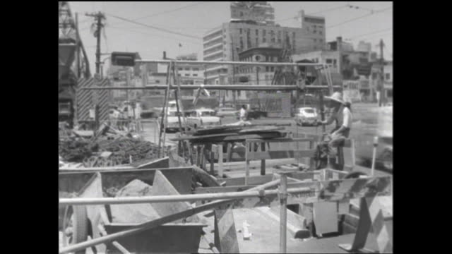 subway construction materials are piled beside a ginza street as pedestrians and vehicles move past. - showa period stock videos & royalty-free footage