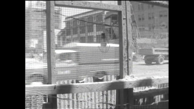 A subway construction site beside a Ginza street is screened in with wire mesh for safety.