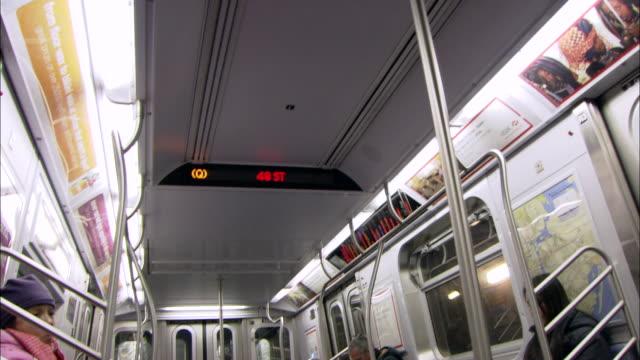 ms td subway interior of moving mta train and digital sign showing stops / new york, new york, united states - 乗り物内部点の映像素材/bロール