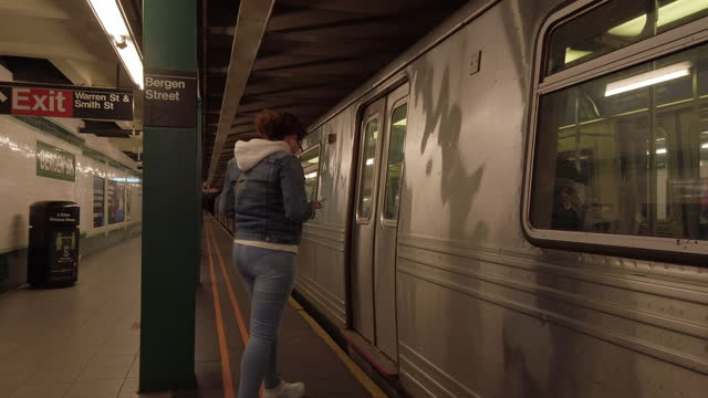subway new york city during pandemic. woman looking at iphone while waiting for arriving train. train arrives and she boards the train. - underground station platform stock videos & royalty-free footage