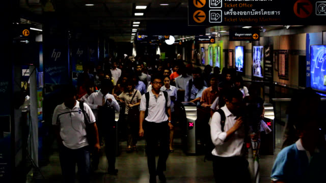 vídeos de stock e filmes b-roll de subway or underground station commuters moving through ticket barriers in bangkok, thailand - torniquete divisa