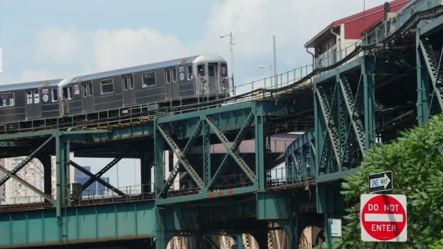 subway runs on elevated railroad at queens new york. - hochbahn passagierzug stock-videos und b-roll-filmmaterial