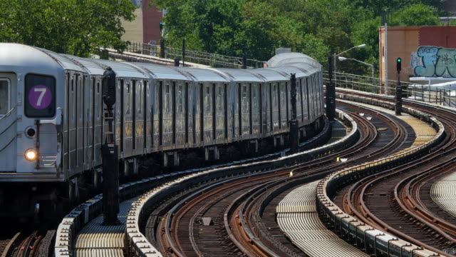 subway runs on winding elevated railroad at queens new york. the railroad goes through the residences area. - queens stock-videos und b-roll-filmmaterial