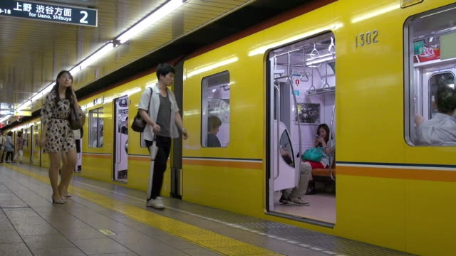 subway stoping and passages entering train in tokyo, japan. - bahnreisender stock-videos und b-roll-filmmaterial