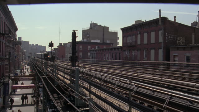 ws subway track with train approaching and people walking on street below - b roll stock videos & royalty-free footage
