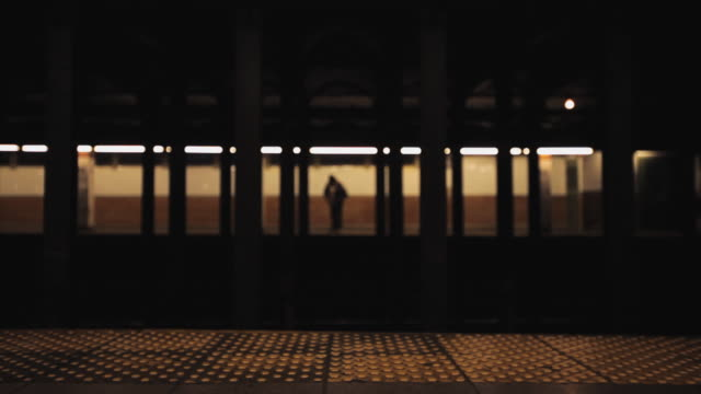 MS Subway train and man waiting at opposite subway platform / New York City, New York, USA