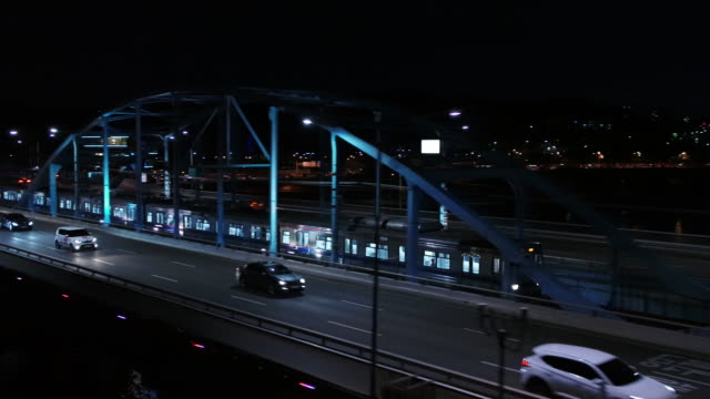 subway train and traffic moving on dongjakdaegyo bridge over han river at night / seoul, south korea - railway bridge stock videos & royalty-free footage