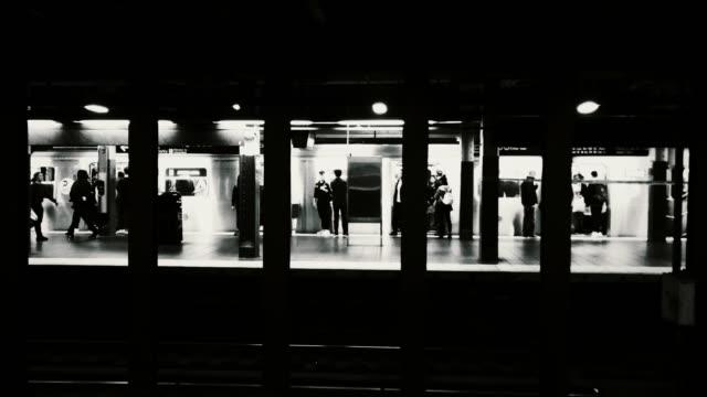 subway train arriving at the train station - bahnreisender stock-videos und b-roll-filmmaterial