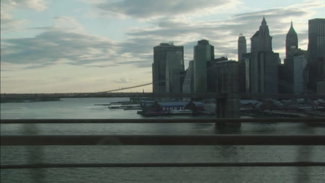 ws pov subway train crossing east river with view of manhattan financial district and brooklyn bridge / new york, new york, usa - brücke stock-videos und b-roll-filmmaterial