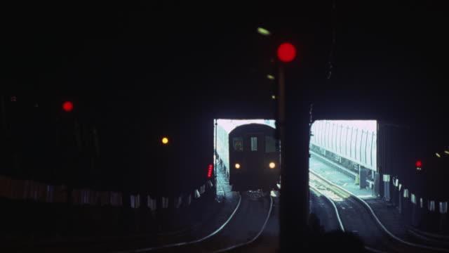 A subway train entering an underground tunnel.