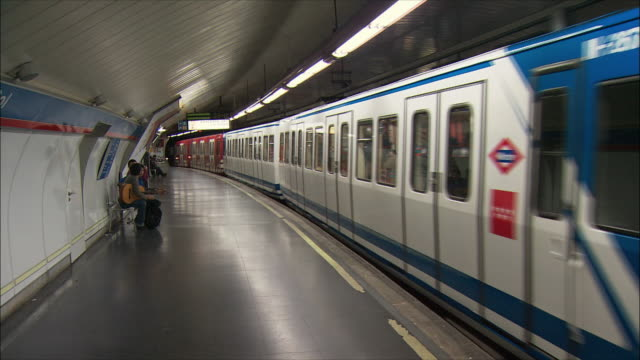 ws pan subway train leaving station, madrid, spain - 2004 stock-videos und b-roll-filmmaterial