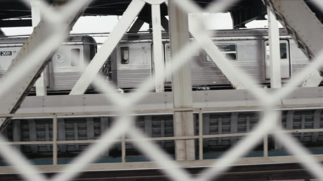 subway train moving on bridge seen through fence - railing stock videos & royalty-free footage
