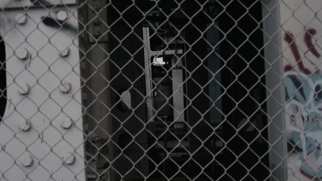 金属製のフェンスを通して見える橋の地下鉄列車 - グラフィティ点の映像素材/bロール