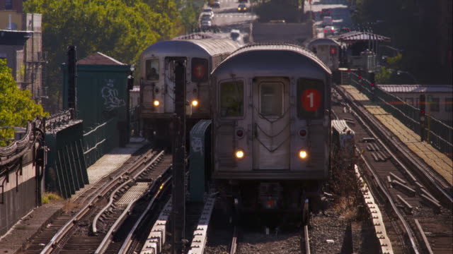 subway train passes by another sitting on center tracks as another waits at station in background. - ハーレム点の映像素材/bロール