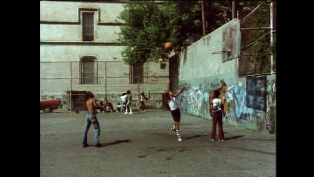subway train passes by outdoor basketball court; 1976 - bbc archive stock-videos und b-roll-filmmaterial