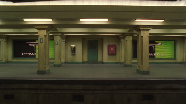 WS Subway train passing an empty station platform