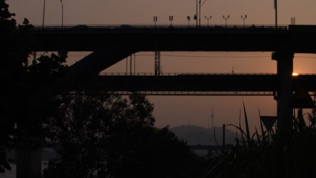 subway train passing through cheongdamdaegyo bridge at sunset / gwangjin-gu, seoul, south korea - swaying stock videos & royalty-free footage