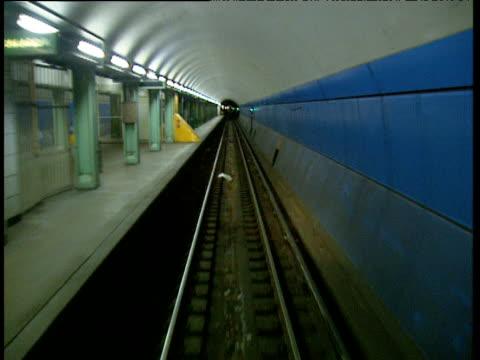 vídeos de stock e filmes b-roll de subway train racing through empty platform approaching underground tunnel - metro de chicago