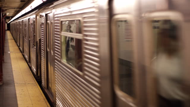 ws subway train rolling through underground station   pan with moving cars as train exits - bahnreisender stock-videos und b-roll-filmmaterial