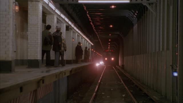 a subway train rolls down tracks. - bahnreisender stock-videos und b-roll-filmmaterial