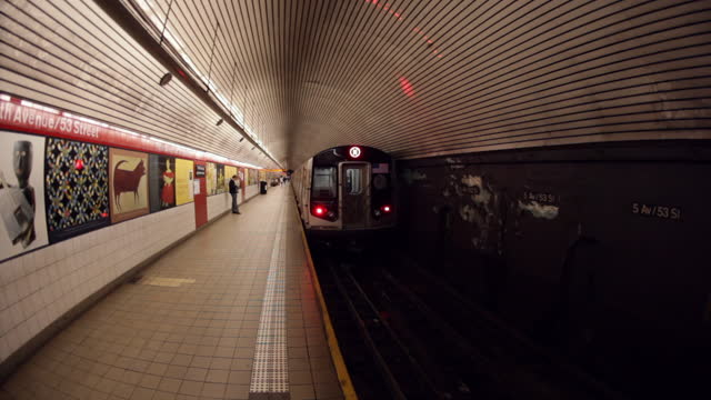 WS subway train slowly exits the station then gains speed   one man waits on platform