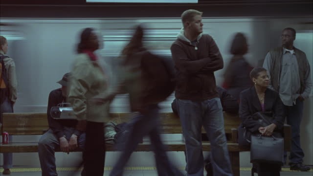 stockvideo's en b-roll-footage met a subway train speeding past commuters waiting at a subway station in new york city. - armen over elkaar