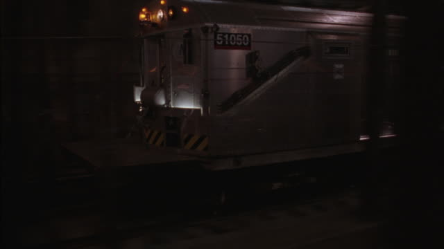 A subway train speeds through an underground tunnel.