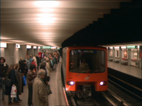 subway train stops beside crowded platform / brussels - 1992 stock-videos und b-roll-filmmaterial