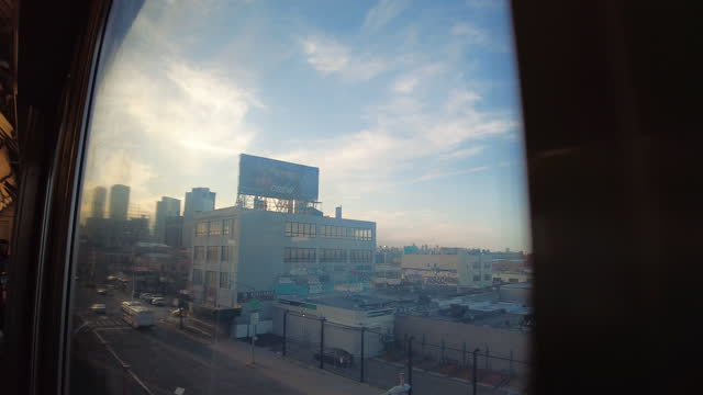 subway train window view from queens into manhattan. manhattan midtown skyline in the distance. driving by a yellow taxi depot, a liquor store, a car... - yellow taxi stock videos & royalty-free footage