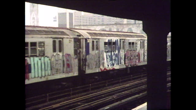 subway trains travel past camera on elevated rails; 1976 - street name sign stock-videos und b-roll-filmmaterial