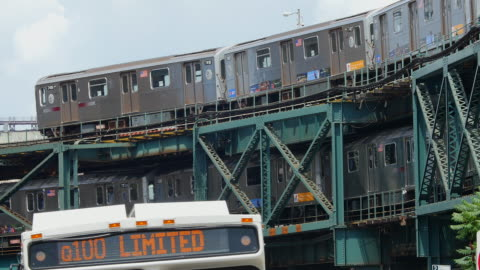 subways run on elevated railroad at queens new york. buses cross in front of camera. - elevated train stock videos & royalty-free footage