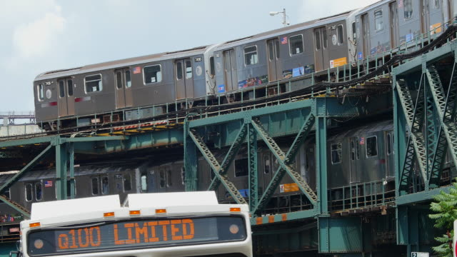 vidéos et rushes de subways run on elevated railroad at queens new york. buses cross in front of camera. - train aérien
