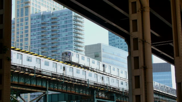 Subways run on elevated railroad which is surrounded by new highrise residences.