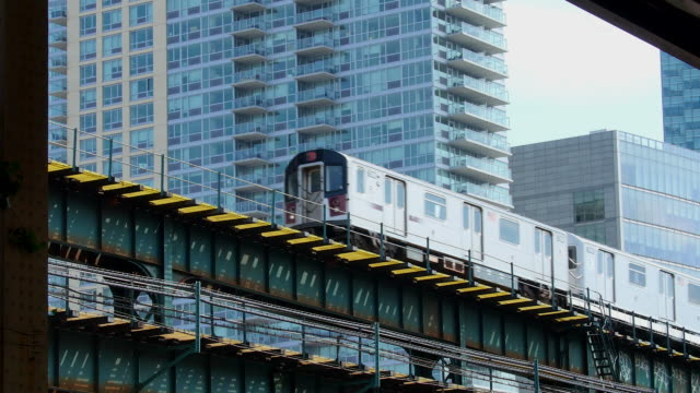 subways run on elevated railroad which is surrounded by new highrise residences. - queens new york city stock videos & royalty-free footage
