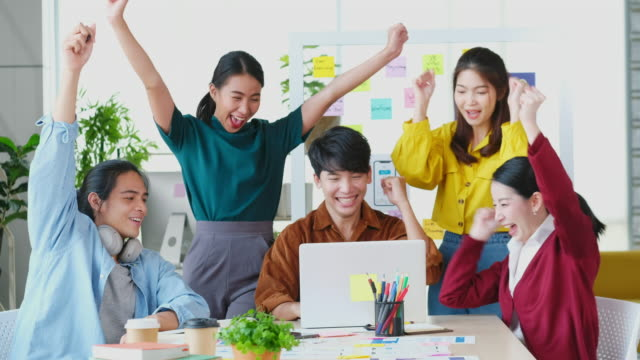 success in business, group of asian creative business team arms raised for a good new,  young asia teamwork celebration for winning project at meeting room office, happy, positive contented emotion - ecstatic stock videos & royalty-free footage