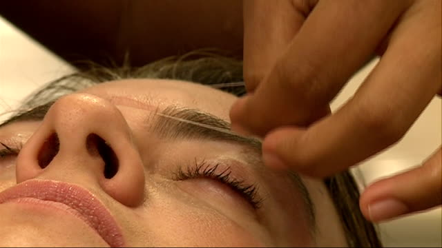blink eyebrowthreading bars 1592011 england london selfridges int general views client having her eyebrows threaded by beautician at blink brow bar... - beautician stock videos and b-roll footage