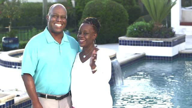stockvideo's en b-roll-footage met succesvolle afro-amerikaanse echtpaar thuis bij zwembad - rijk staat