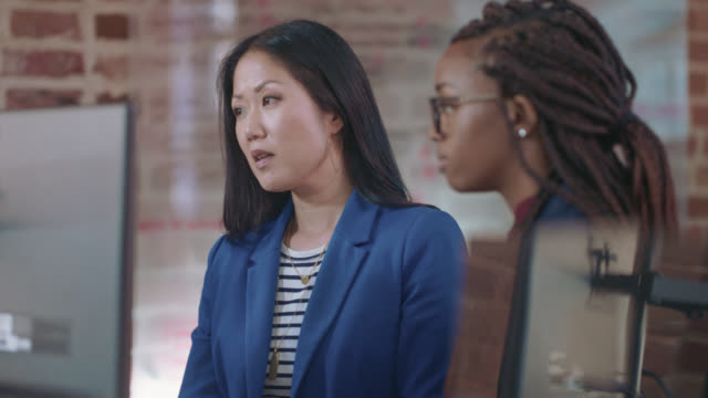 successful asian businesswoman mentors a young colleague as they exchange ideas together - braided hair stock videos & royalty-free footage