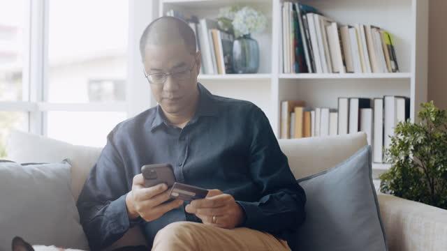 vídeos de stock e filmes b-roll de successful asian man making payment online. - one mature man only