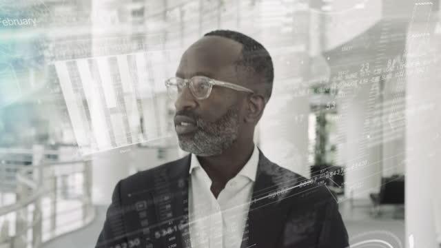 successful black business man executive walking in modern office lobby with stock market data graph - 最高経営責任者点の映像素材/bロール