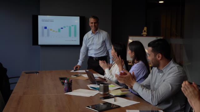 stockvideo's en b-roll-footage met succesvolle business man het afwerken van een presentatie en collega's applauwerden zeer vrolijk - diavoorstelling