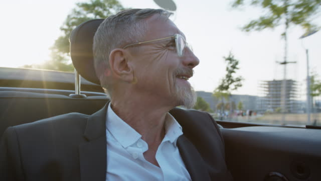 successful business man in his early 60s with short greying hair and grey beard enjoys urban lifestyle in summer, he wears a black garment while getting chauffeured in a convertible. - old convertible stock videos & royalty-free footage