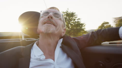 successful business man in his early 60s with short greying hair and grey beard enjoys urban lifestyle in summer, he wears a black garment while getting chauffeured in a convertible. - grey hair stock videos & royalty-free footage