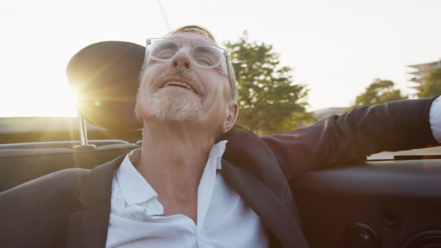successful business man in his early 60s with short greying hair and grey beard enjoys urban lifestyle in summer, he wears a black garment while getting chauffeured in a convertible. - auto convertibile video stock e b–roll