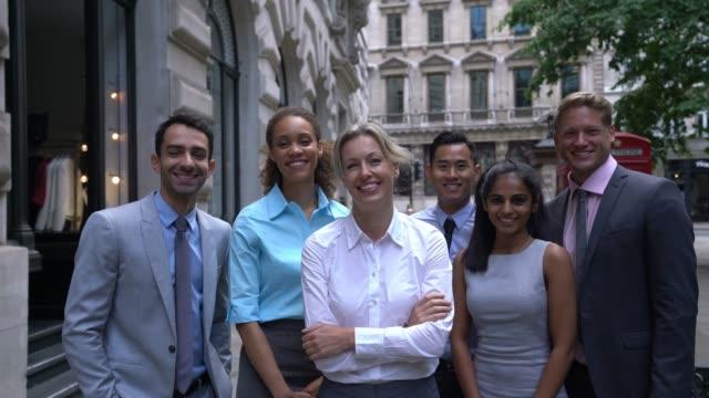 vidéos et rushes de équipe réussie d'affaires tout souriant à l'appareil-photo et le dirigeant féminin avec des bras croisés - cravate