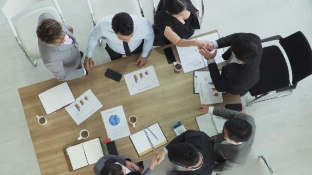 vídeos de stock, filmes e b-roll de equipe bem sucedida do negócio que dá cinco elevados e que agitam a mão do outro na reunião - mesa de reunião