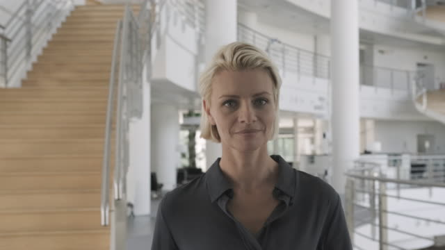 successful business woman executive walking in modern office lobby and looking into camera confident - short hair stock videos & royalty-free footage